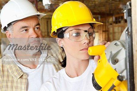 Arbeiterin schneiden Holz mit einer macht sah, während männliche Arbeiter hinter