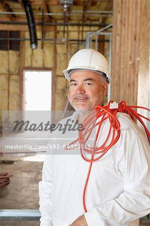 Porträt von Bauarbeiter mit einem roten elektrischen Draht