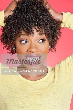 Afroamerikaner, die seitlich mit den Händen im Haar über farbigen Hintergrund schauen