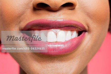 Nahaufnahme Detail einer afroamerikanischen Frau lächelnd über farbigen Hintergrund