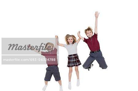 Portrait d'écoliers heureux, main dans la main tout en sautant sur fond blanc