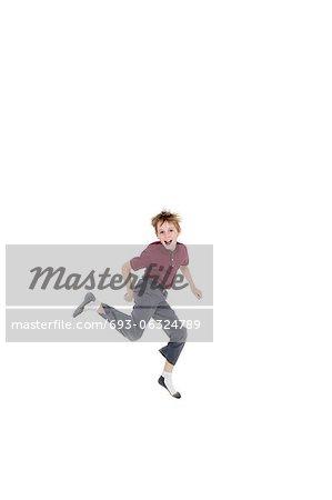 Portrait de gai garçon pré-ado sautant sur fond blanc