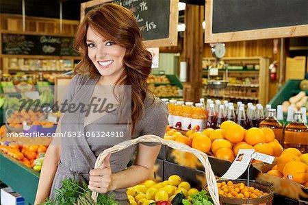 Portrait of a happy brunette woman standing with basket in fruit market