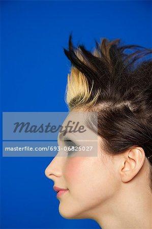 Vue latérale d'une jeune femme aux cheveux hérissés sur fond coloré