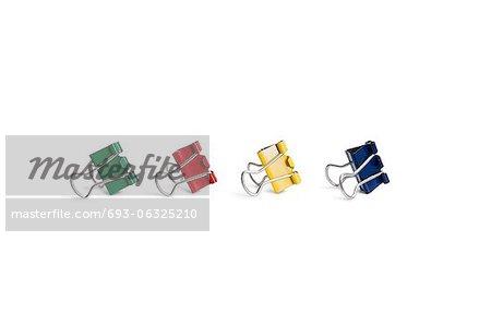 Multicolored bulldog clips over white background
