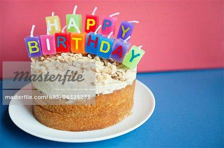 Nahaufnahme der Geburtstagskerzen auf Torte Kuchen über farbigen Hintergrund