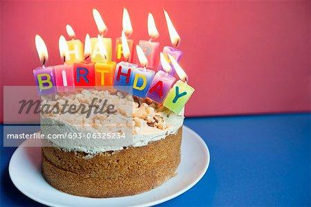 Nahaufnahme der Kerzen brennen auf Geburtstagstorte auf farbigen Hintergrund