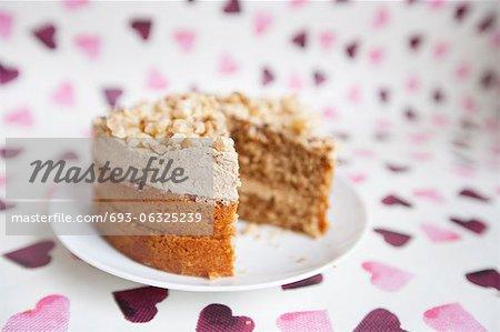 Nahaufnahme des Kuchens mit fehlenden Stück über Herz geformt Hintergrund