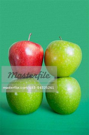 Pile de pommes rouges et vertes sur fond coloré