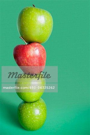 Pommes rouges et vertes sur fond coloré d'équilibrage