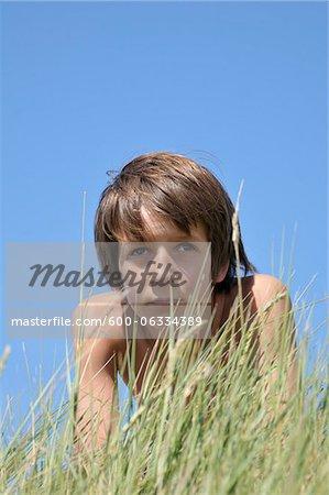 Portrait de garçon couché dans l'herbe, Ile de ré, France