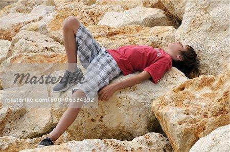 Garçon allongé sur les rochers, Ile de ré, France