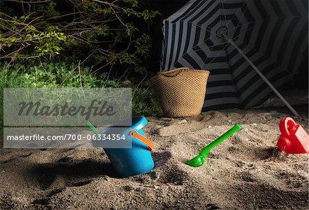 Toys and Sun Umbrella on Beach at Night