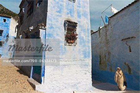 Femme qui marche entre les bâtiments, Chefchaouen, Province de Chefchaouen, région de Tanger-Tétouan, Maroc