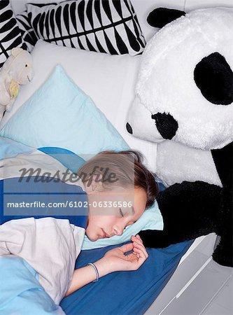 Fille de dormir dans son lit avec teddy bear