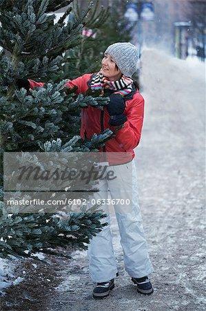 Smiling woman choosing Christmas tree