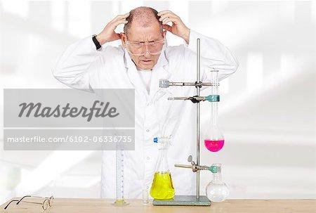 Scientist holding head over beaker in laboratory