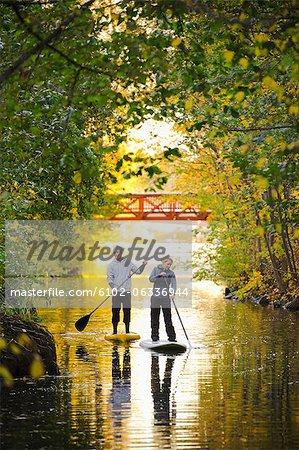 Deux personnes paddle conseils d'aviron dans les arbres de l'automne