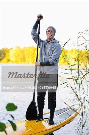 Portrait of man on paddle board in water
