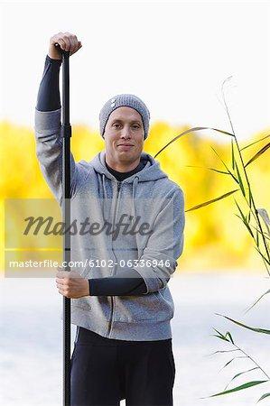 Portrait of man holding oar outdoors