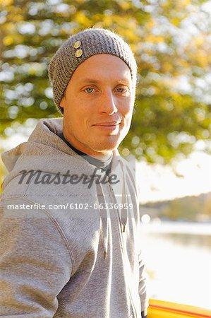 Homme au bonnet en tricot souriant à l'extérieur