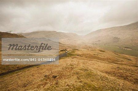 Schauen unten in Duddon Valley von der Spitze des Hardknott-Passes, Autos, aufsteigend. Lake District-Nationalpark, Cumbria, England, Vereinigtes Königreich, Europa