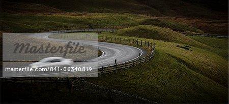 Silber Sportwagen fahren durch das kurvenreiche Straße in Peak-District-Nationalpark, Derbyshire, England, Vereinigtes Königreich, Europa