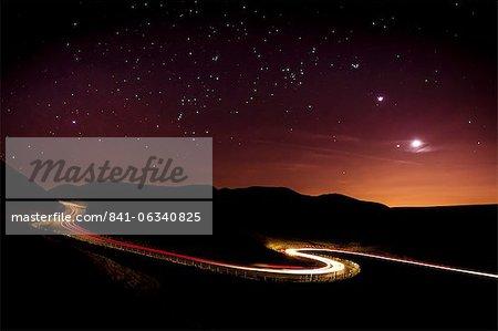 Licht Routen und Sterne Cape mit Venus, Jupiter, Orion und der Mond deutlich sichtbar über eine kurvenreiche Straße in den Peak District National Park. Derbyshire, England, Vereinigtes Königreich, Europa