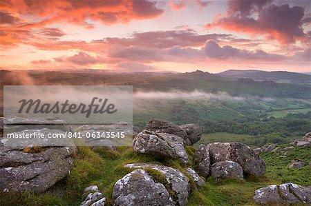 Dramatic sunset above a misty moorland near Hound Tor, Dartmoor National Park, Devon, England, United Kingdom, Europe