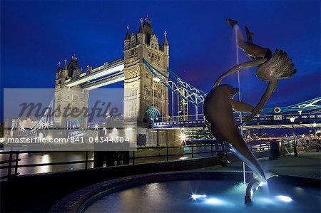 Fille avec un dauphin, statue de David Wynne, éclairée la nuit devant le Tower Bridge, Londres, Royaume-Uni, Europe