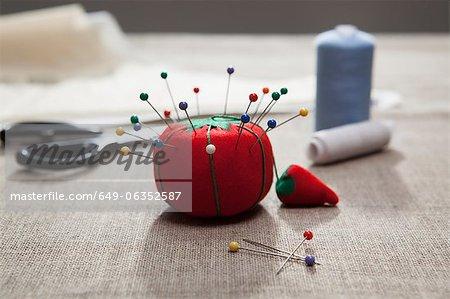 Pin cushion, thread and scissors