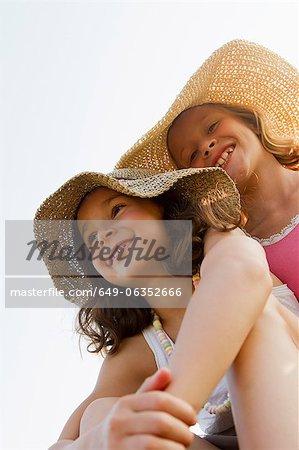 Sourire de jeunes filles portant des chapeaux de soleil en plein air