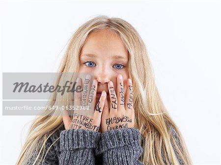 Mädchen für Gesicht mit Schreiben an Händen