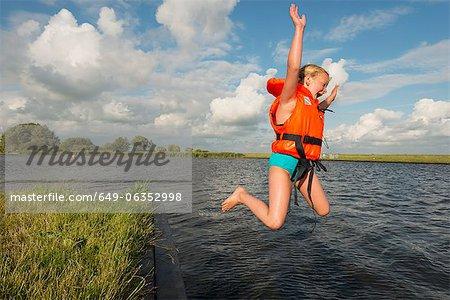 Jeune fille sautant dans le lac rural
