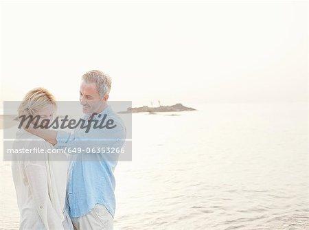 Älteres Paar umarmt am Strand