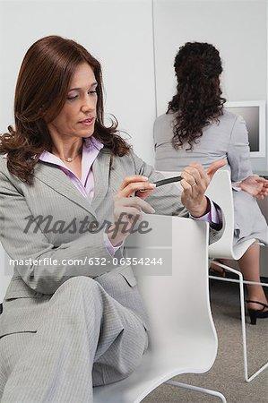 Geschäftsfrau, die Einreichung ihrer Nägel bei der Arbeit