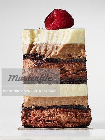 Ein Stück von geschichteten Schokoladenkuchen, gekrönt mit einer Himbeere