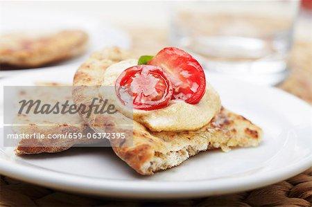 Pita-Brot belegt mit Hummus und Kirschtomate