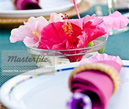 Ein Gedeck und eine Schale mit Wasser Hibiskusblüten