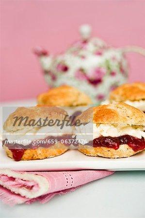 Scones avec confiture de fraises et de crème avec un pot de thé en arrière-plan