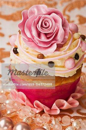 Un petit gâteau décoré avec un sucre rose rose et crème au beurre