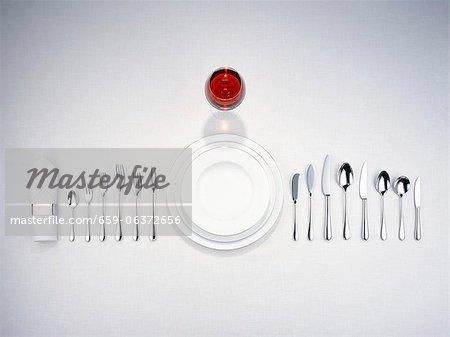 Teller, Besteck, eine Serviette und ein Glas Rotwein