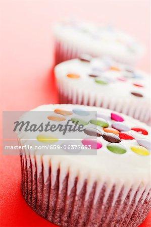 Weiße kleine Kuchen verziert mit farbigen Schokolade Bohnen