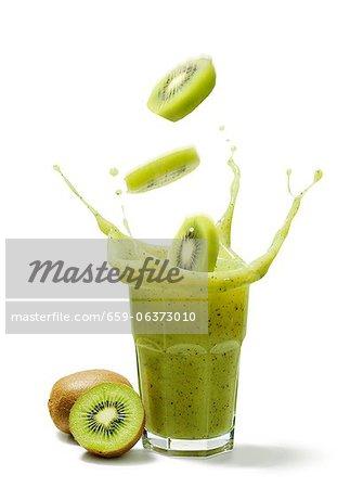 Tranches de kiwi, tomber dans un verre de jus de kiwi