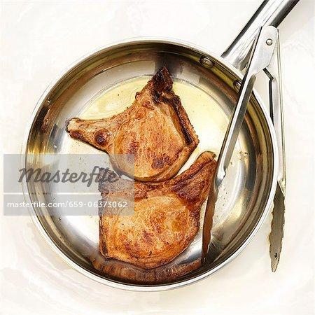 Deux poêlé désossé côtelettes de porc dans une poêle à frire