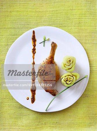 Ente Beinchen mit Sellerie-Blüten auf einem weißen Teller; Von oben