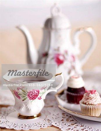 Ziemlich antiken Teetasse mit Mini-Muffins und Teekanne