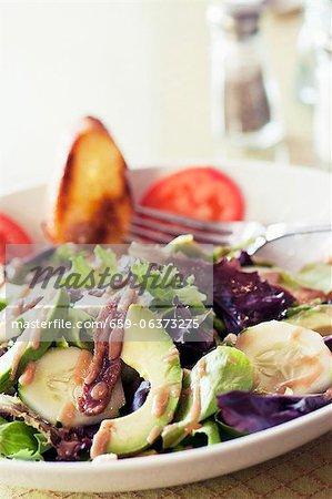Portion de salade à l'anchois, avocat, concombre et mesclun