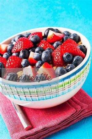 Eine Schale mit Erdbeeren, Blaubeeren und Müsli