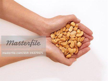 Hände halten geschälte Nüsse
